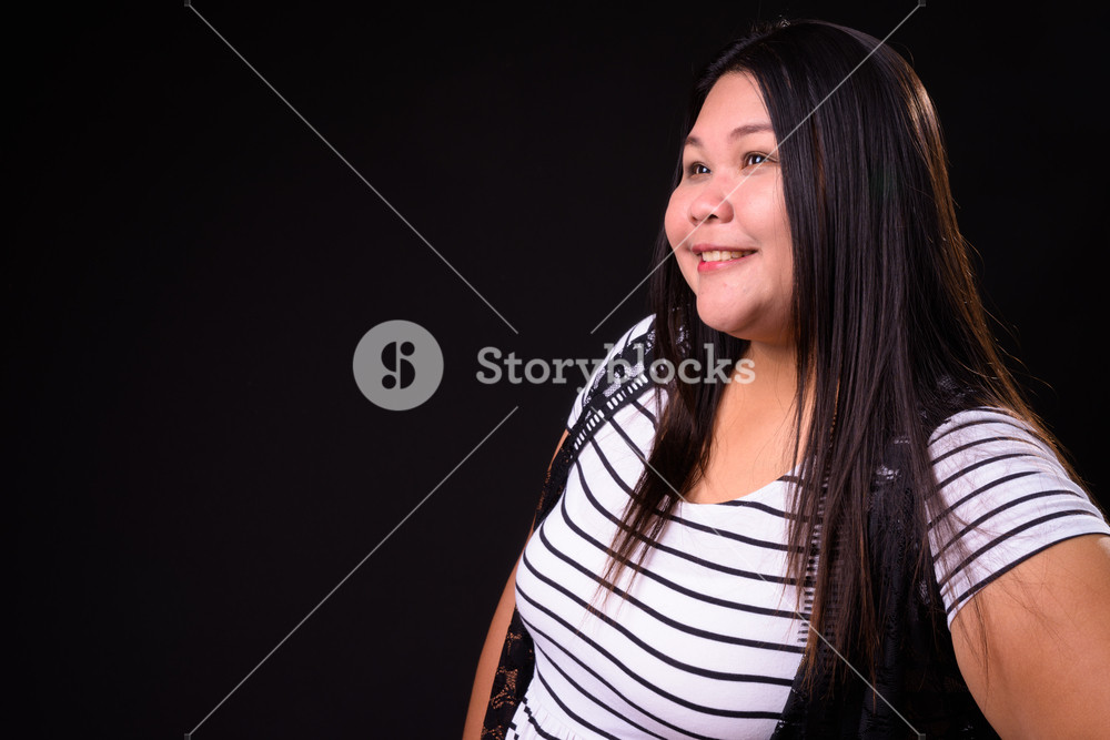 Beautiful overweight Asian woman against black background Royalty 1000x667