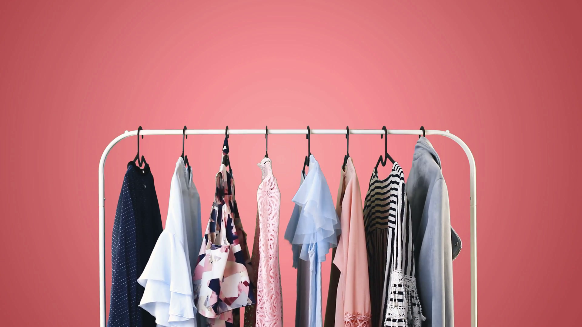 Womens clothing on a white clothes hanger on pink pastel 1920x1080