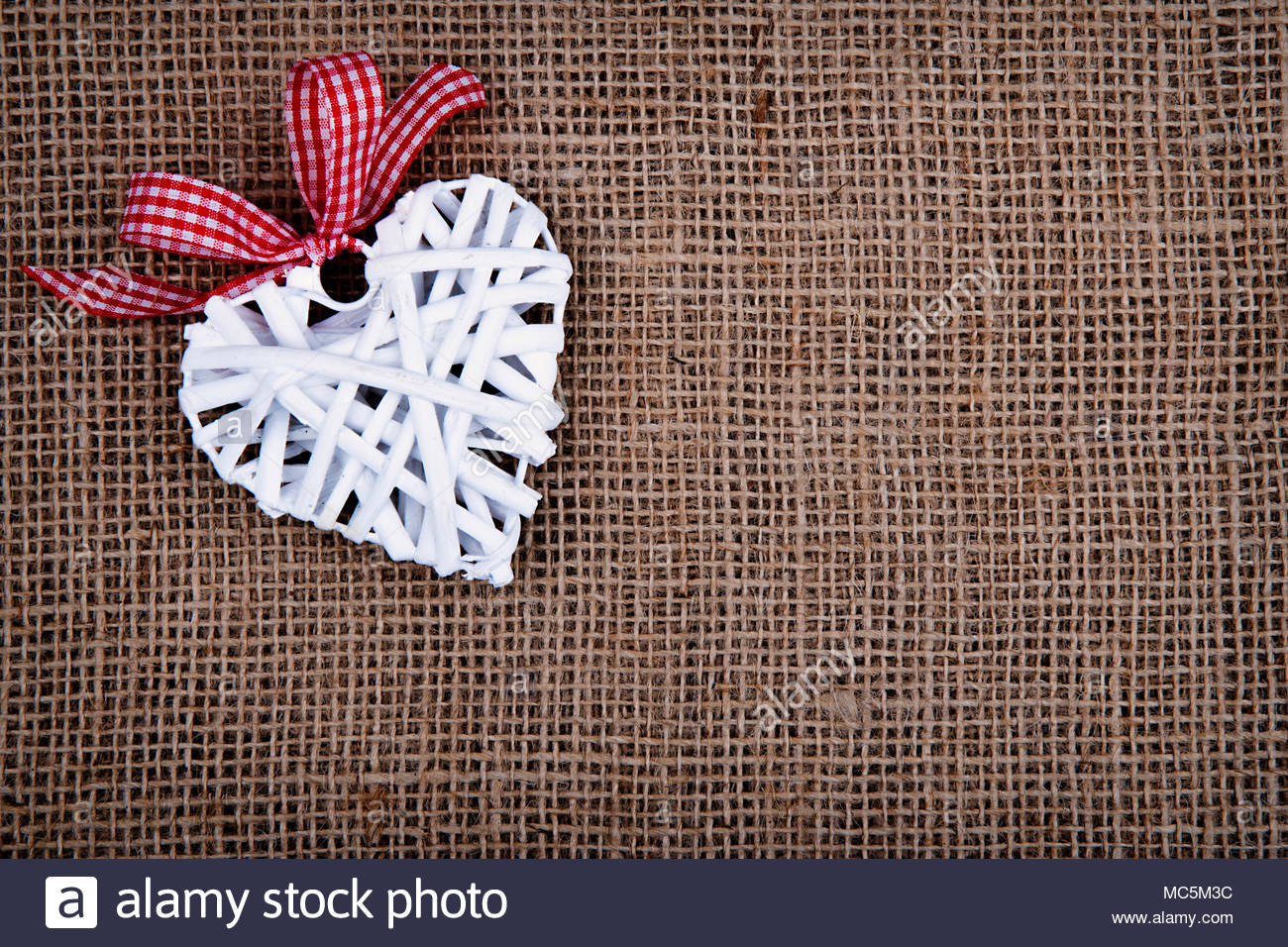 White raffia heart with red ribbon on the burlap background Stock 1300x956