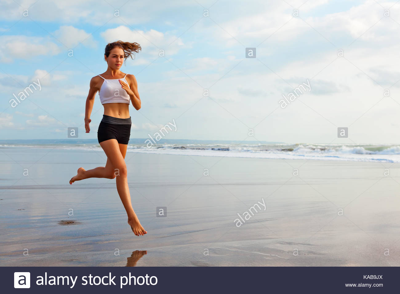 Barefoot sporty girl with slim body running along sea surf by 1300x956