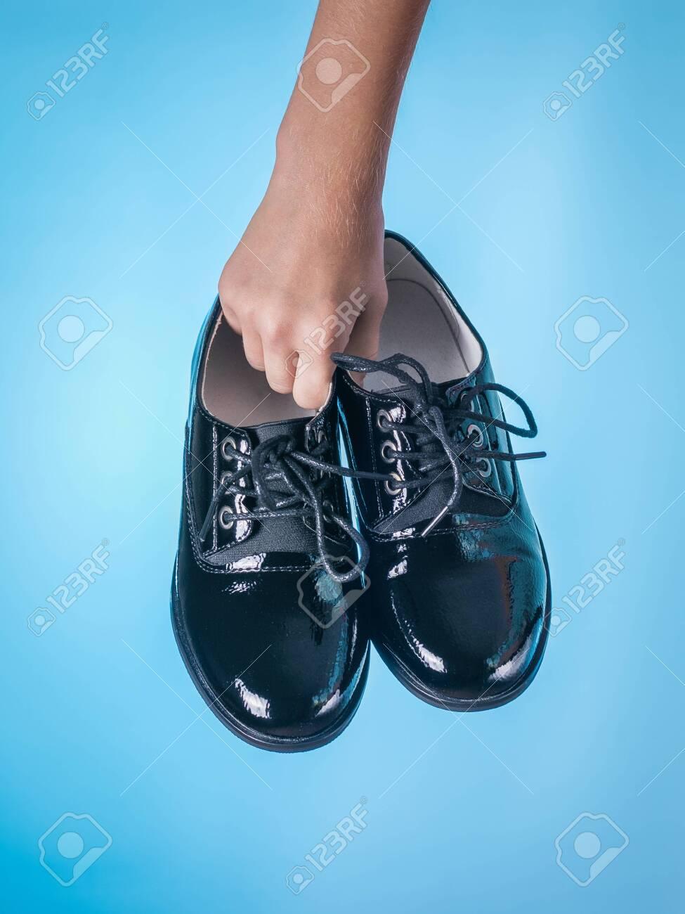 Fashionable Patent Leather Womens Shoes In Hands On A Blue 975x1300