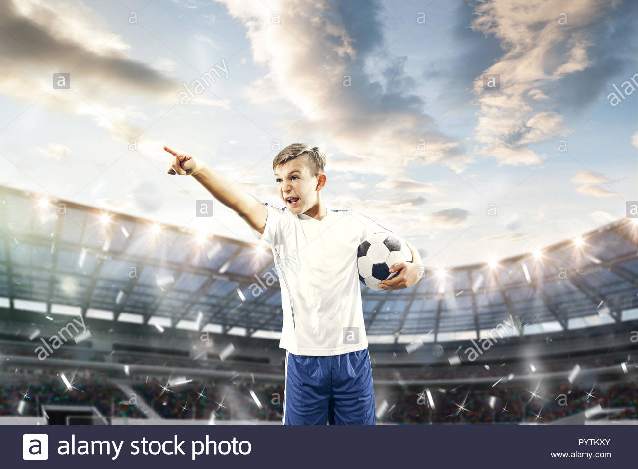 Young boy with soccer ball doing flying kick at stadium football 1300x956