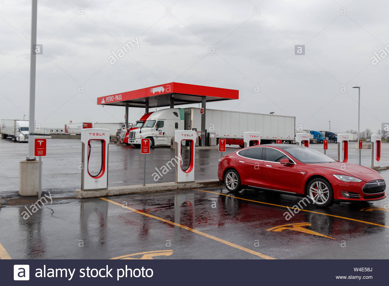 Tesla Supercharger Station with red Model S charging truck stop 1300x956