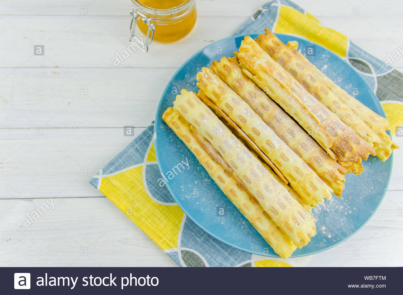 homemade waffle tubes on a blue plate on white background with 1300x951