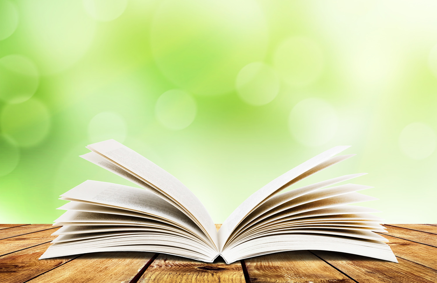 Open book on a table with a blurred leafy background 1500x972
