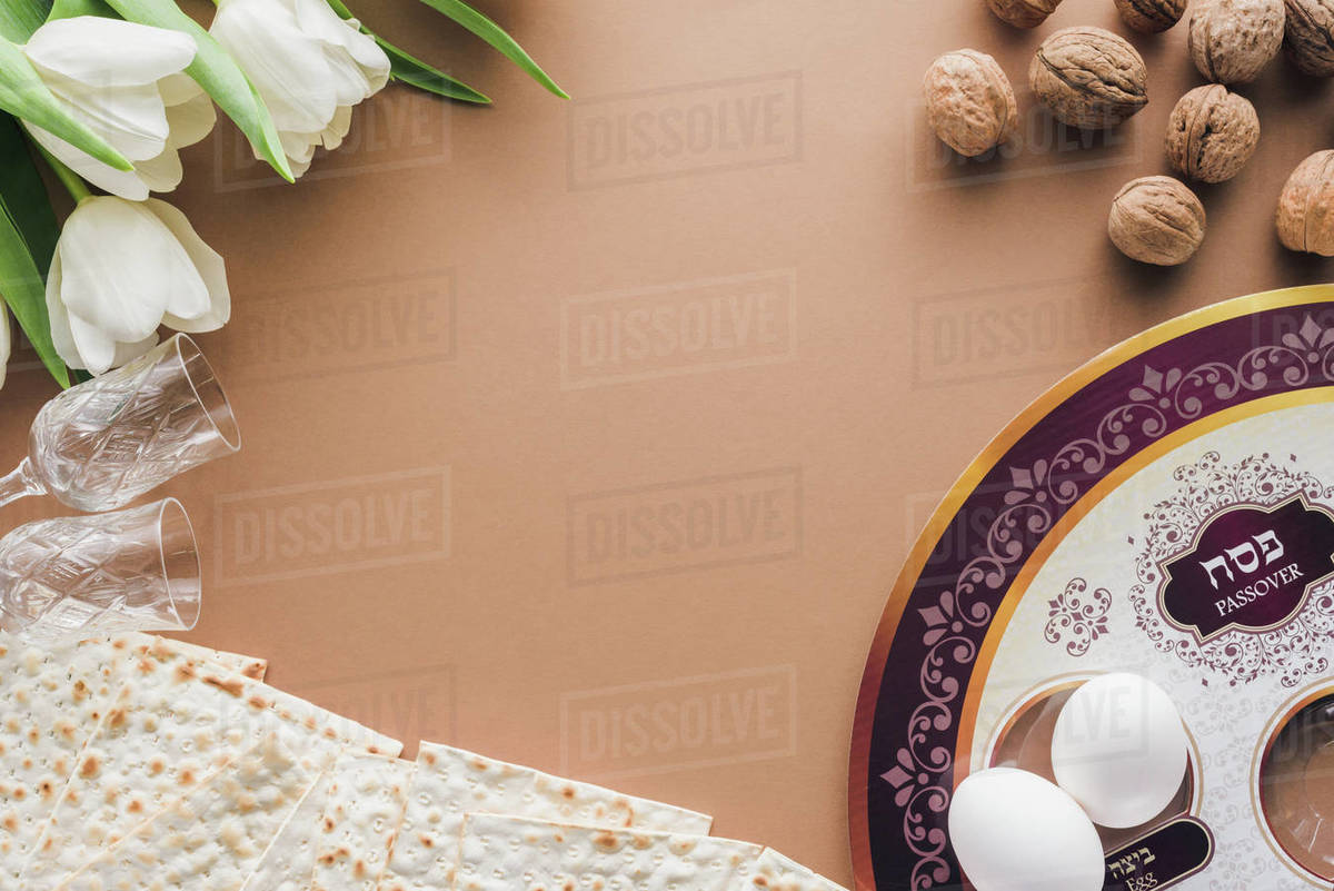 Top view of traditional Jewish plate and matzah on beige table 1200x801