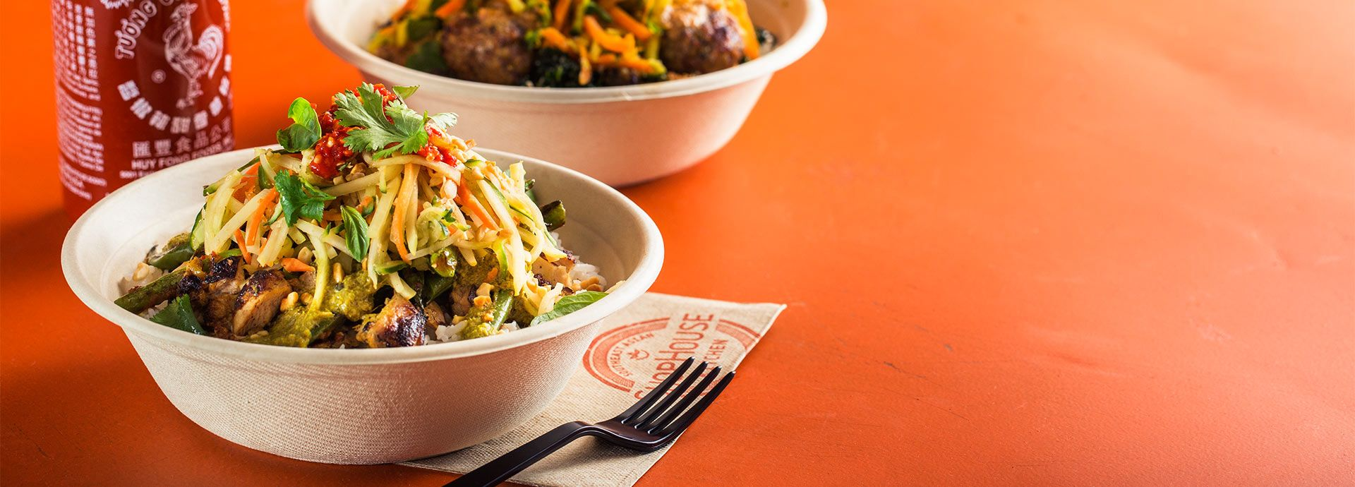 Shophouse Kitchen bowl with Sriracha sauce in background Food 1920x690