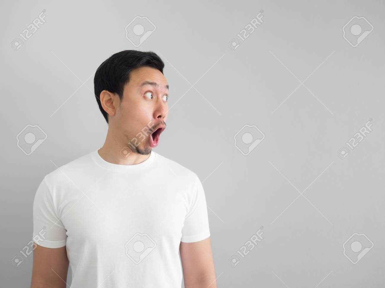 Shocked Face Of Asian Man In White Shirt On Grey Background Stock 1300x975