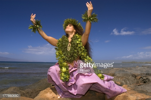 Hula dancer with haku lei in traditional outfit on shoreline ocean 508x338