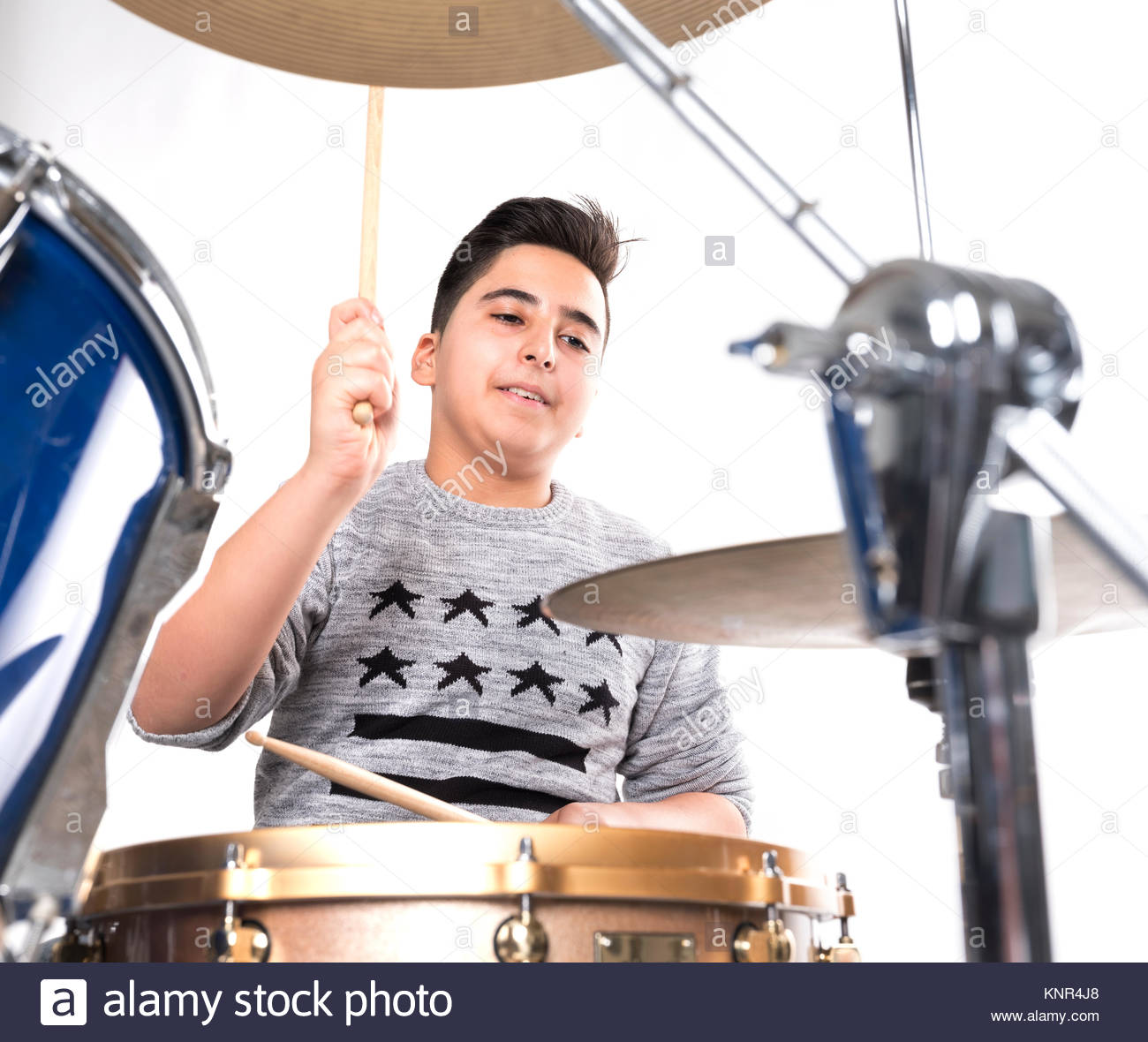 teen boy at drumset in studio against white background Stock Photo 1300x1180