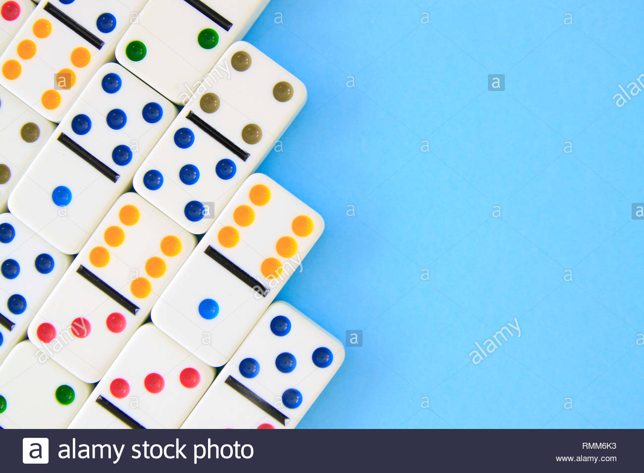 White dominos with brightly colored dots on blue background shot 1300x956