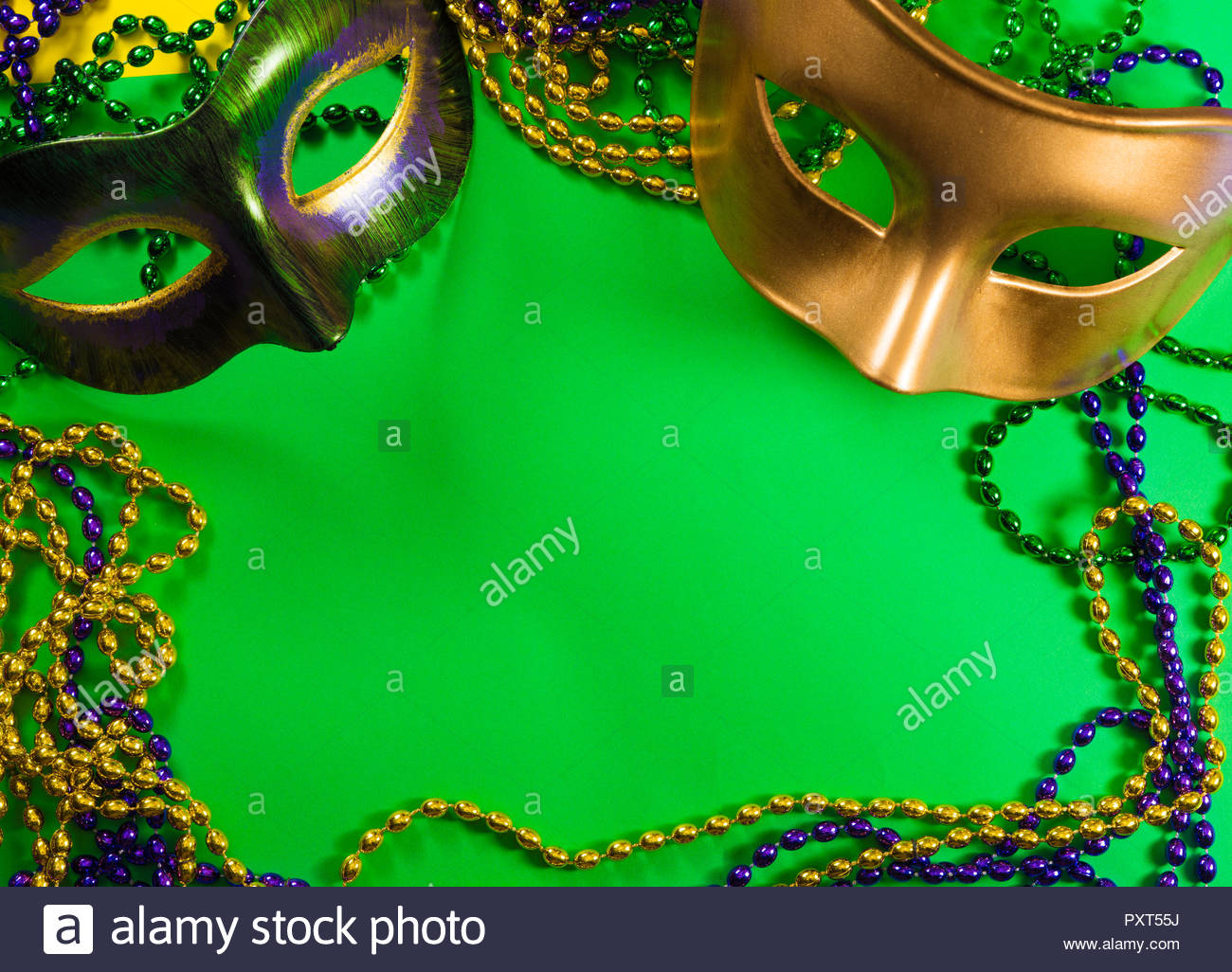 Mardi Gras mask with beads on a green background Stock Photo 1300x1026