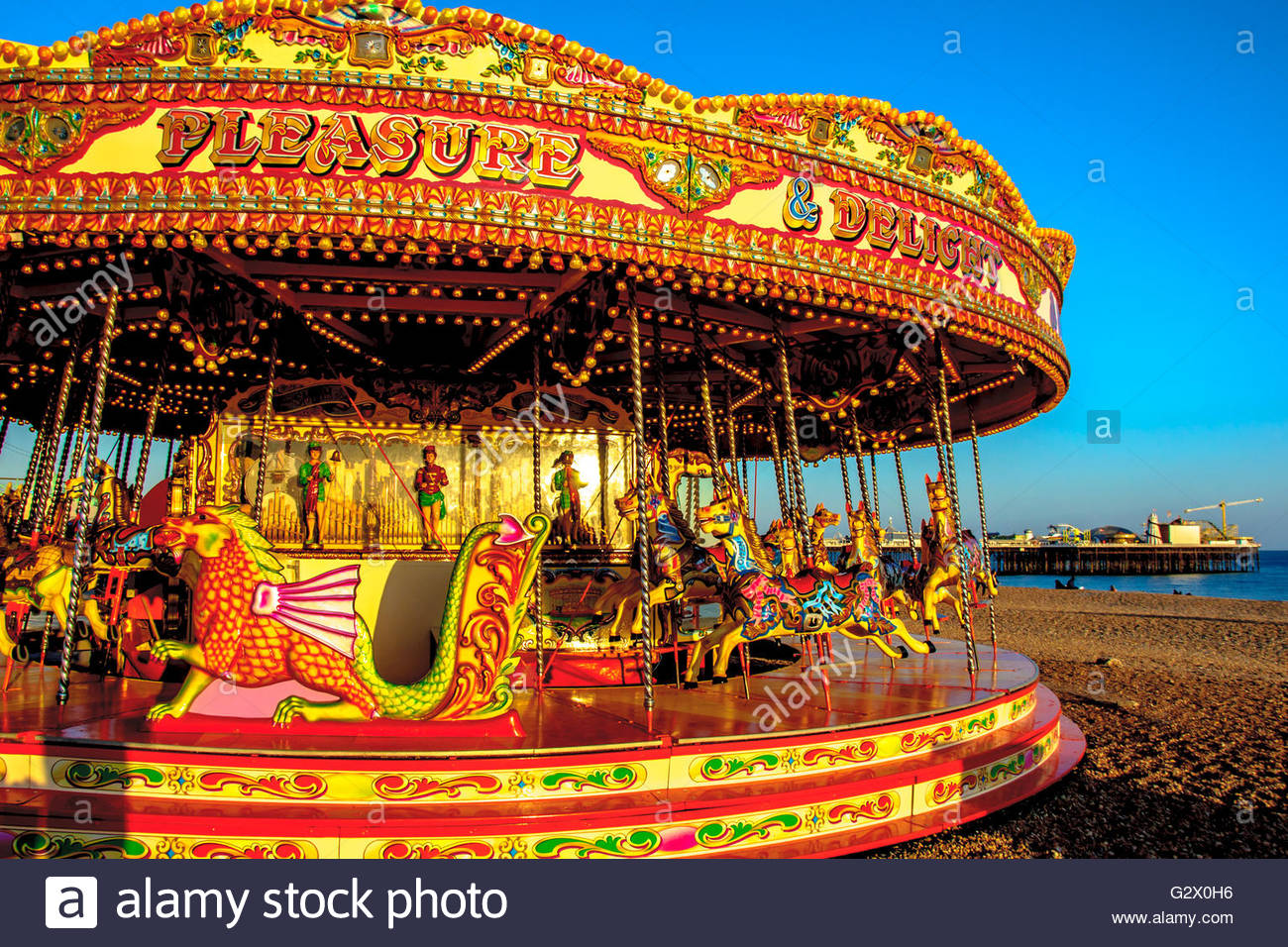 A carousel on Brighton beach with pier on background East Sussex 1300x956
