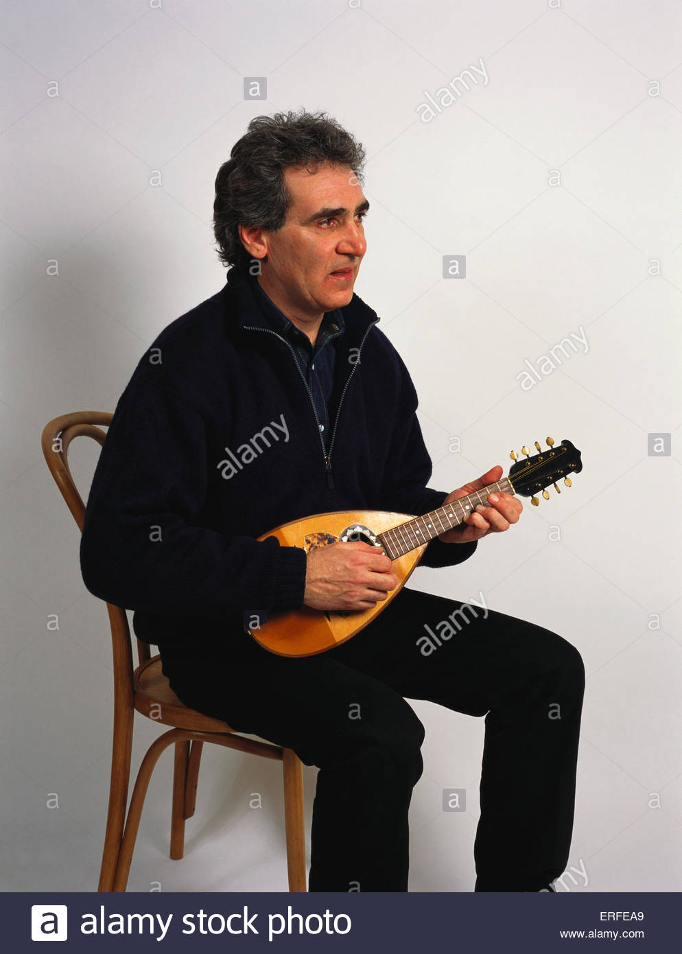 Mandolin being played by a seated man Sitting White background 994x1390