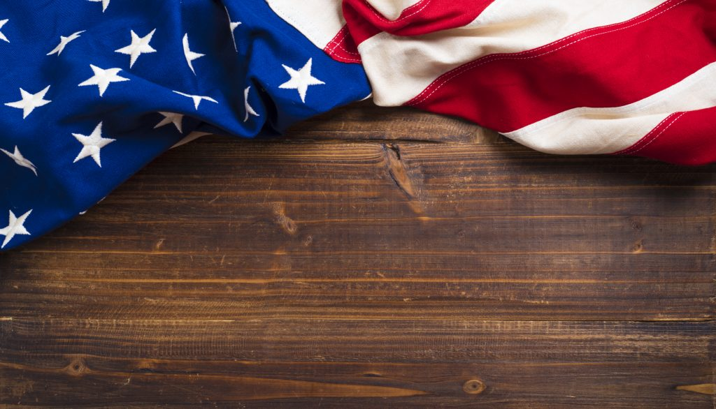 Old American Flag on wooden plank background 1024x586
