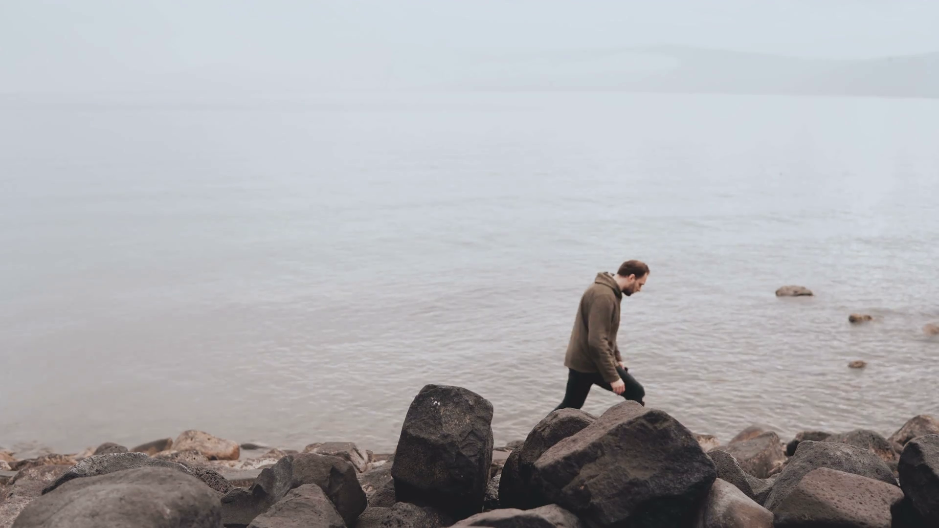 Caucasian man at the edge of Sea of Galilee Big stones shore of 1920x1080