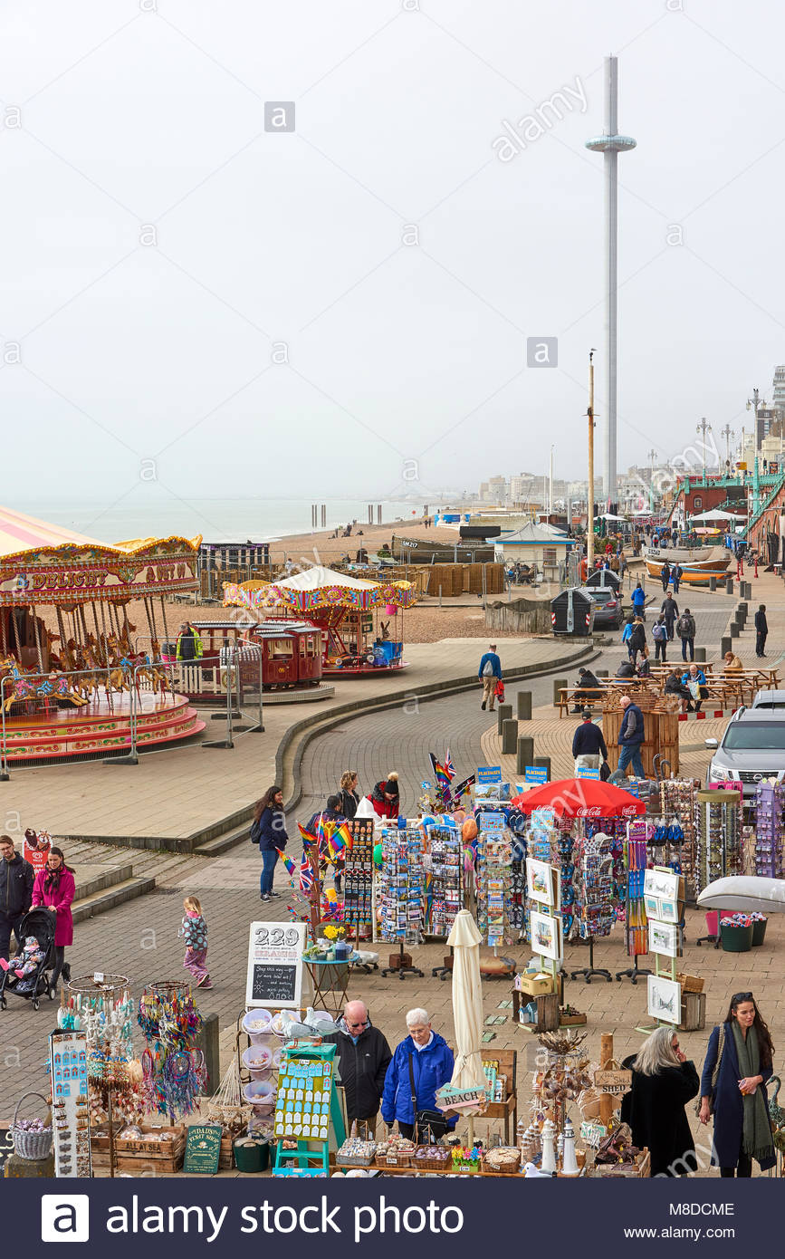 High angle shot of Brighton beach promenade with souvenir shops in 867x1390