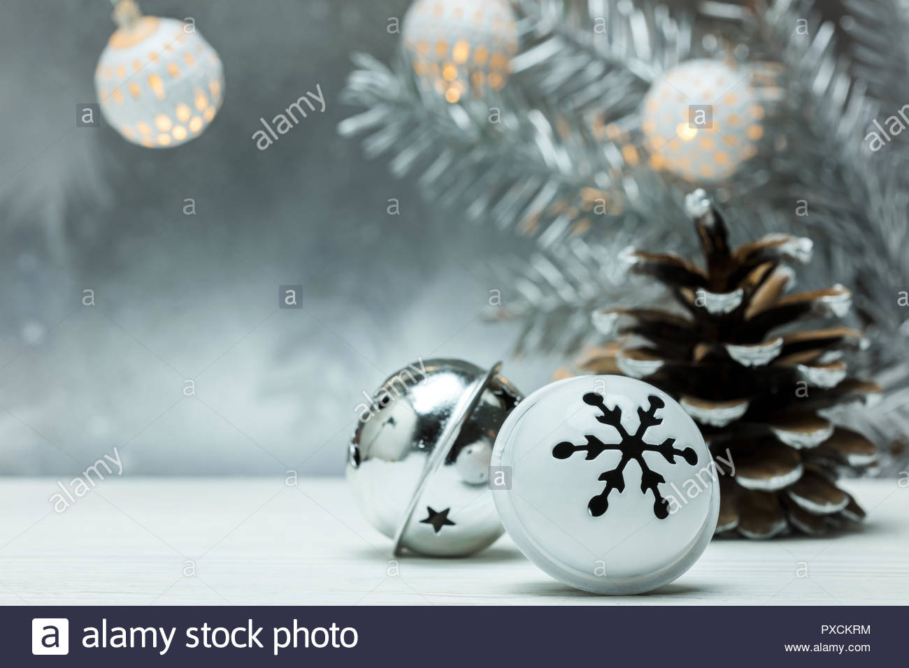 silver pine cone and christmas jingle bells on gray blurred 1300x956