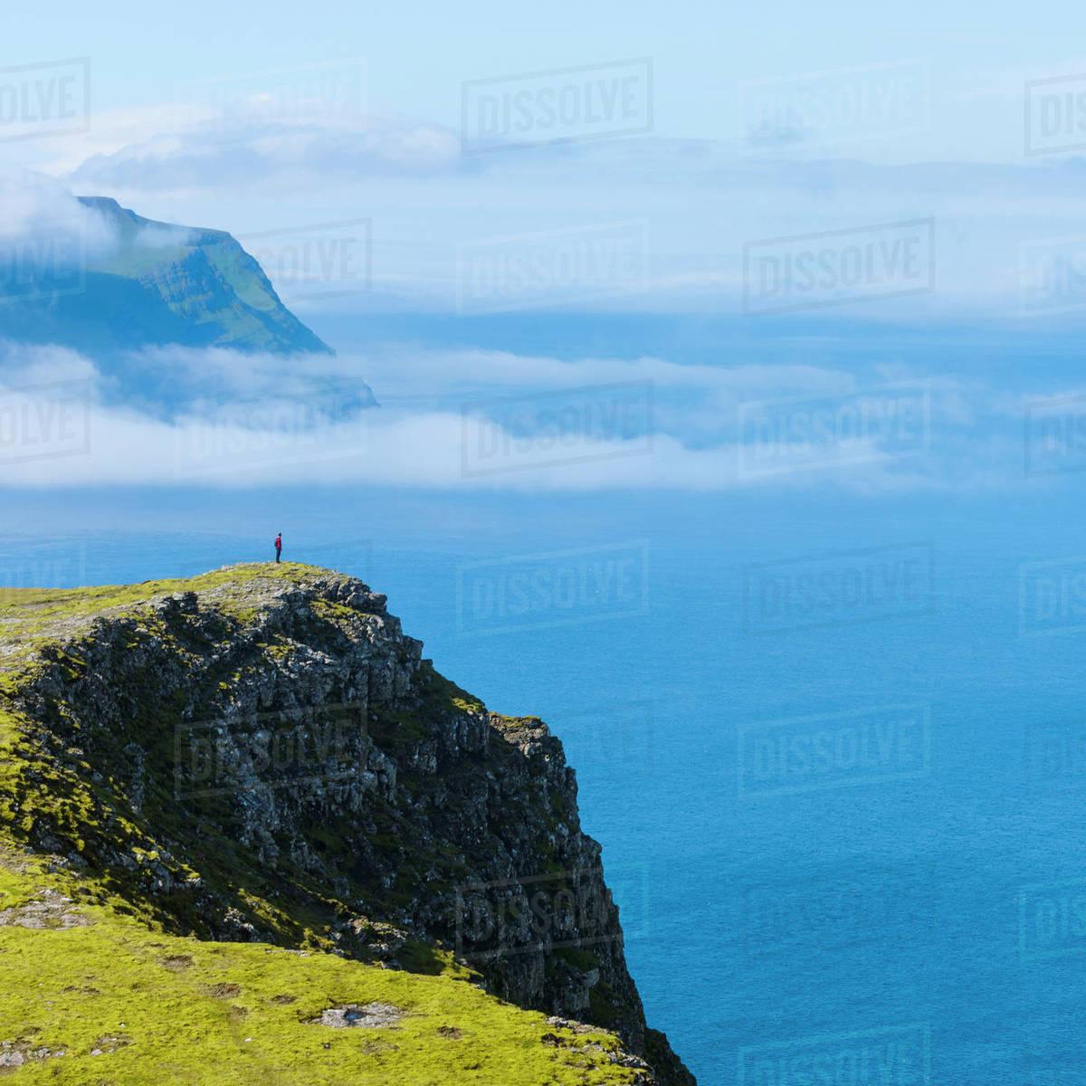 Seaside cliffs person on background   Stock Photo   Dissolve 1200x1200