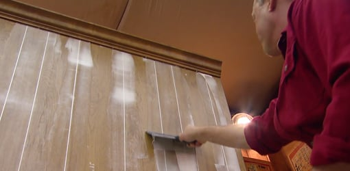 Smoothing out joint compound in paneling grooves with a drywall knife 510x250