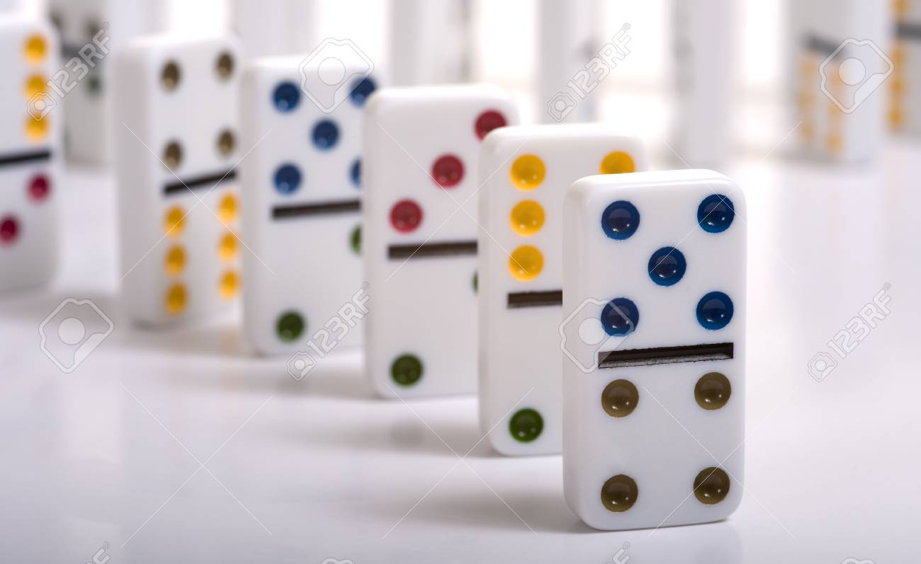 A Row Of Dominos Standing On A White Background Stock Photo 1300x797