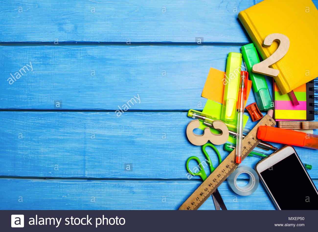 A pile of school supplies on a blue wooden table background The 1300x951